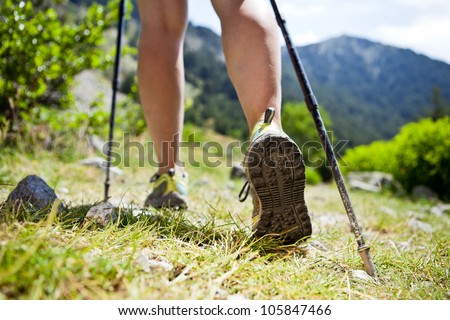 Woman hiking in mountains, adventure and exercising. Legs and nordic walking poles in summer nature. - stock photo