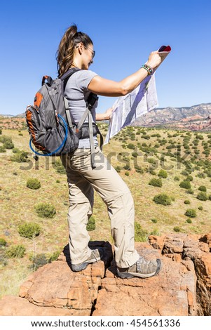 Woman hiking locates position on a map - stock photo