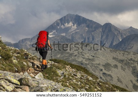 woman hiking on mountain ridge in Pirin Mountain, Bulgaria and Kamenitsa Peak in background