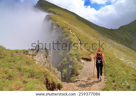 Woman hiking on the mountain edge near the clouds - stock photo