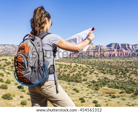Woman hiking viewing map location - stock photo