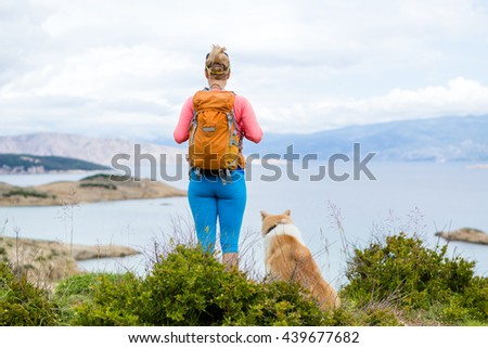 Woman hiking with akita inu dog on seaside trail. Recreation and healthy lifestyle outdoors in summer mountains and sea nature. Beautiful inspirational landscape. Travel trekking and activity concept. - stock photo