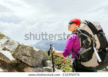 Woman hiking with backpack in mountains, climbing and trekking in Corsica France - stock photo