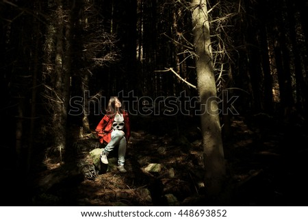 woman hipster traveler sitting in sunlight in woods in mountains, smiling, travel concept, atmospheric moment
