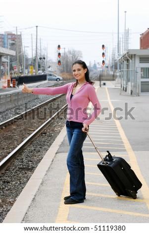 woman hitchhiking at railroad station - stock photo