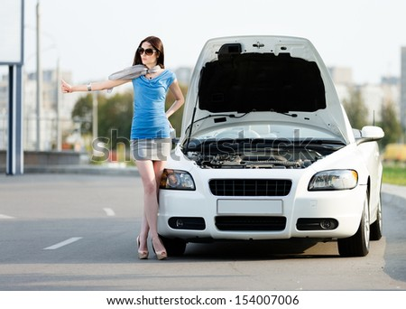 Woman hitchhiking near the opened hood of the broken car and waiting for assistance - stock photo