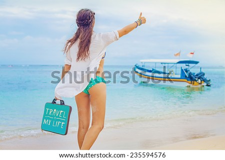 woman hitchhiking on a beach (back view, faceless) - stock photo