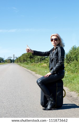 woman hitchhiking on a lonely road with her thumb up - stock photo