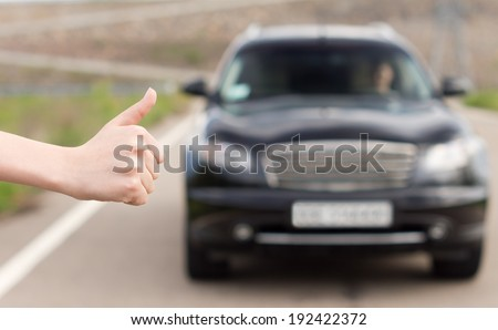 Woman hitchhiking soliciting a ride holding her hand out into the road in a thumbs up gesture to draw the attention of an approaching motorist