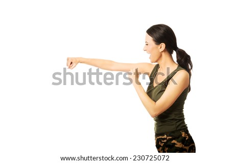 Woman hitting punching bag, shouting loud and wearing military clothes.