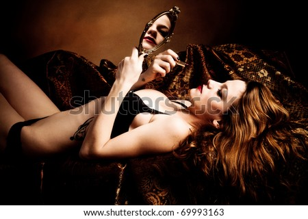 woman hold hand mirror and apply lipstick, lie on bed, golden brown background, studio shot