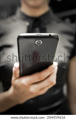 Woman holding a big black smartphone in hand - stock photo