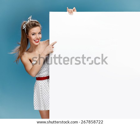 Woman holding a blank billboard on blue background / photo set of young American pin-up model on blue background with space for text - stock photo