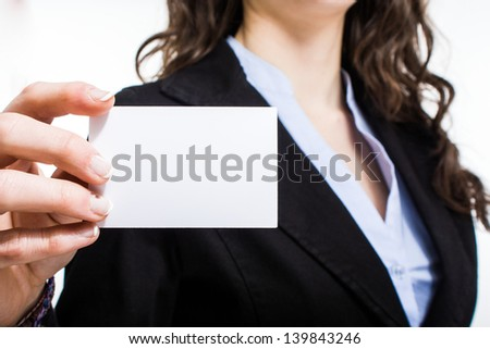 Woman holding a blank business card - stock photo