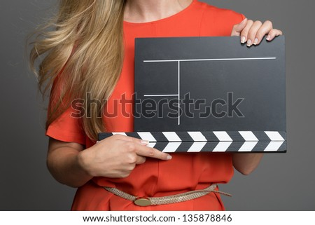 Woman holding a blank clapper board slate on a film set with copyspace for your details of time and the number of the take