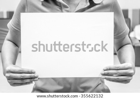 Woman holding a blank paper sheet with both hands. - stock photo