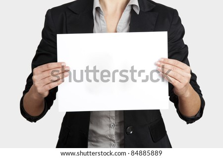 Woman holding a blank paper sheet with both hands - stock photo
