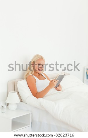 Woman holding a book in her bedroom