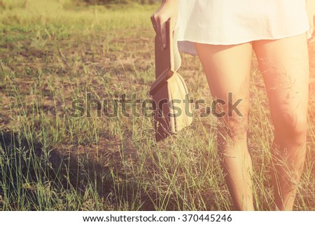 Woman holding a book in meadows on the sunshine of morning. - stock photo