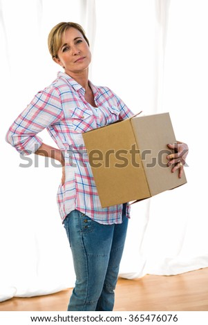 Woman holding a box feeling lower back pain
