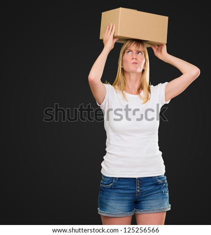 woman holding a box on her head against a black background - stock photo