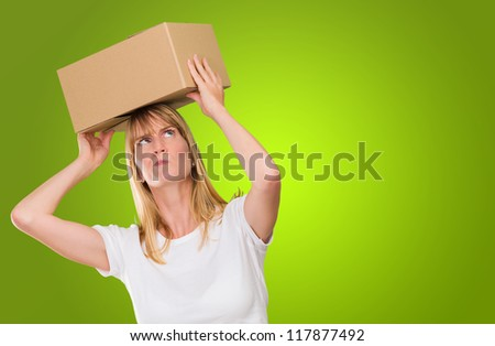 woman holding a box on her head against a green background - stock photo