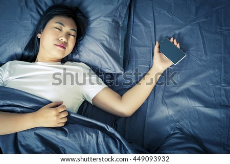 Woman holding a cell phone to sleep