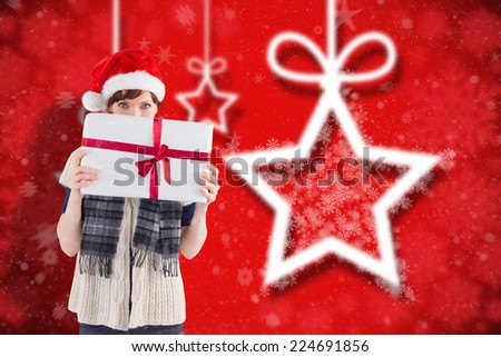 Woman holding a christmas present against blurred christmas background - stock photo