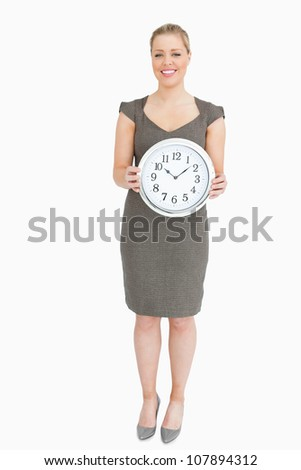 Woman holding a clock against white background - stock photo