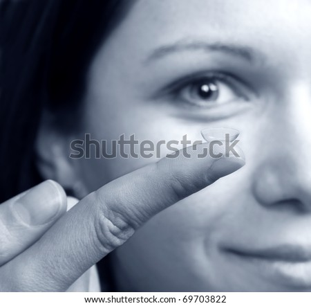 Woman holding a contact lens - stock photo