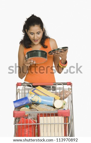 Woman holding a container and looking surprised - stock photo