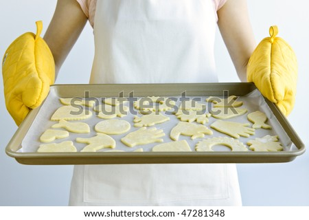 Woman holding a cookie tray with homemade cookies for baking - stock photo
