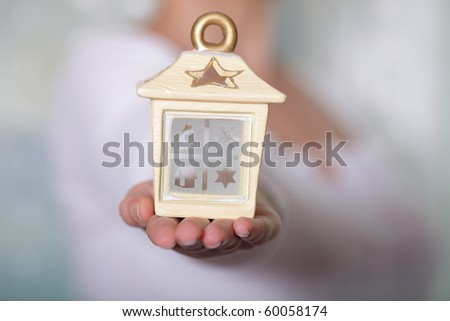 Woman holding a cosy house in her hands - stock photo