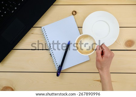 Woman holding a cup of coffee. Empty blank, pen, laptop - stock photo