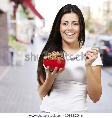 woman holding a delicious red breakfast bowl against a street background