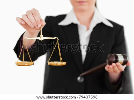 Woman holding a gavel and scales of justice against a white background - stock photo