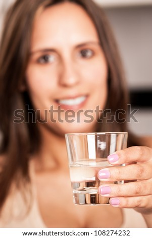 Woman holding a glass of water, she is out-of-focus - stock photo