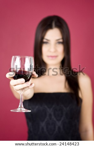 Woman holding a glass of wine - shallow DOF with focus on wine - stock photo