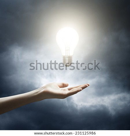 Woman holding a glowing lightbulb in her hand - stock photo
