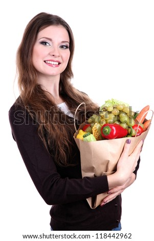 Woman holding a grocery bag full of fresh vegetables and fruits isolated on white