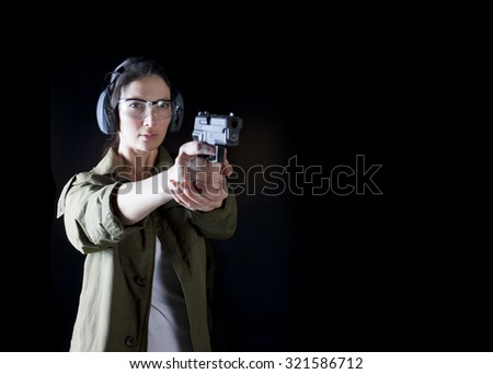 Woman holding a gun with protective gear - stock photo