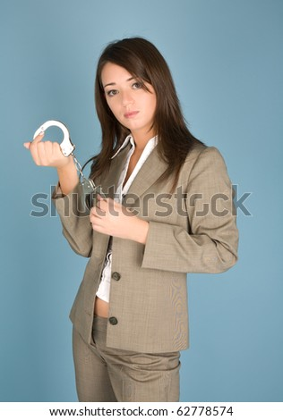 Woman holding a handcuffs standing on the blue background - stock photo