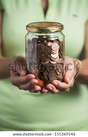 Woman holding a jar full of pennies meaning savings. - stock photo