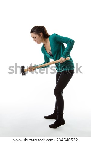 woman holding a large sledgehammer smashing the ground - stock photo