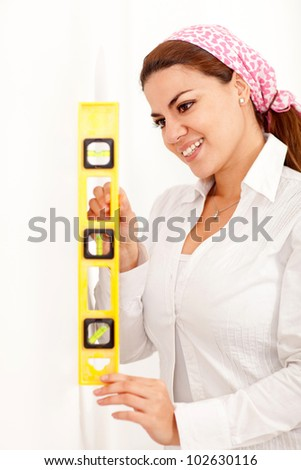 Woman holding a level instrument against the wall and smiling - stock photo
