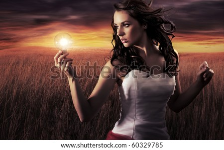 Woman holding a light bulb - stock photo