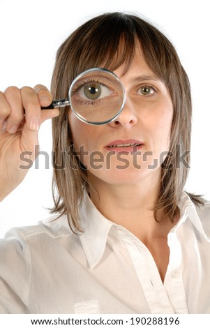 Woman holding a magnifier front of her eye. - stock photo