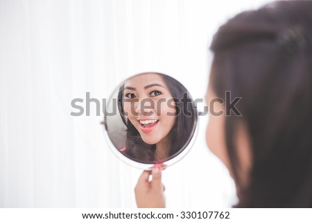 Woman holding a mirror, smiling brightly looking at her face - stock photo