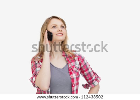 Woman holding a mobile phone while looking up against a white background - stock photo