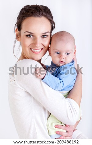 Woman holding a new born child on white background - stock photo